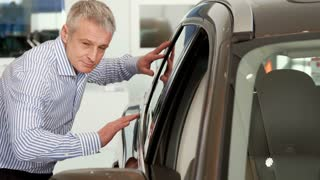Mature man touching the car door at the dealership. Caucasian gray customer cheking the exterior of the vehicle. Middle aged male client leaning on cars roof