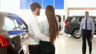 Mature salesman consulting young couple at the car dealership. Sales manager coming to his clients at the car showroom. Gray male consultant showing car to young people