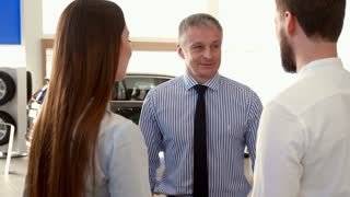 Mature salesman telling the couple about the car at the dealership. Close up of young people discussing purchasing of the car with sales manager. Caucasian clients standing backwards to the camera