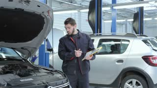 Mechanic examines car at the service