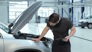 Mechanic examines car fender