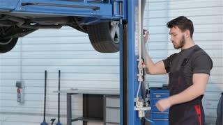 Mechanic lifts car by hydraulic lift