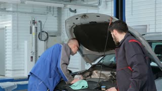 Mechanic troubleshoots car problem at the car service