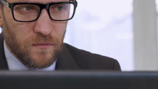 Middle aged businessman working on laptop at the office. Close up of caucasian bearded man in glasses looking at the screen. Attractive serious male manager in suite and tie doing his job