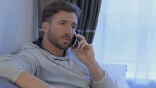 Middle aged man talking on the phone at home. Brunette caucasian man holding his smartphone near his ear. Close up of attractive bearded man calling on the phone