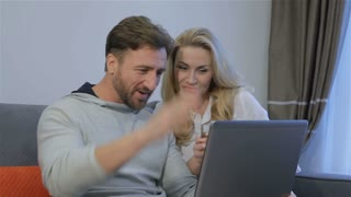 Nice caucasian couple looking at laptop at home. Attractive bearded man showing something on laptop to his pretty blond wife. Handsome brunette man pointing his hand on the laptop screen