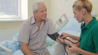 Nurse measures blood pressure of male patient