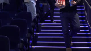 People going away from the movie theater. Low angle shot of people walking downstairs at the cinema. Teens leaving the auditorium after the end of the film