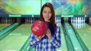 Pretty caucasian girl holding bowling ball in her hands. Attractive brunette lady in checkered shirt smiling for the camera. Beautiful female bowler posing against background of lanes