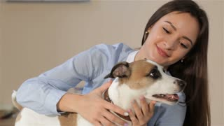 Pretty caucasian woman petting the dog at the veterinarian clinic. Close up of attractive woman smiling for the camera near her dog. Nice Jack Russel Terier wagging his tail while his female owner