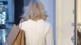 Pretty caucasian woman shopping at the mall. Attractive blond girl turning back near the lingerie boutique. Beautiful young lady walking away with shopping bags on her shoulder