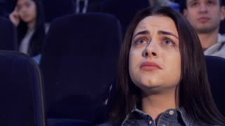 Pretty caucasian woman watching drama at the movie theater. Attractive brown haired girl having sad face at the cinema. Close up of female teenager worrying about film characters