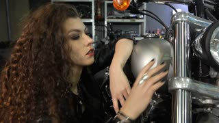 Pretty female biker touching the front fork of the motorcycle. Close up of crouching young curly girl leaning on the gas tank of the chopper by her elbow. Attractive caucasian woman in black leather