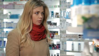Pretty female customer showing her thumb up at the drugstore. Attractive blond woman gesturing good quality of some remedy. Young caucasian woman in red scarf holding box with medicine in her hand