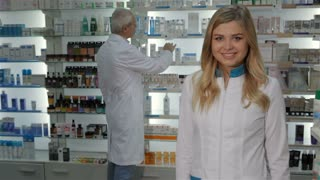 Pretty female pharmacist showing her thumb up at the drugstore. Attractive caucasian female druggist standing against background of display with drugs. Young blond woman gesturing the good quality of