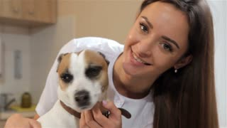 Pretty female veterinarian turning dog's head to the camera. Close up of attractive caucasian woman moving dog's head by her hands. Young caucasian woman in white medical uniform standing near the dog