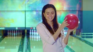 Pretty girl posing with bowling ball. Attractive brunette lady standing against background of pin on the end of lane. Young female bowler looking down