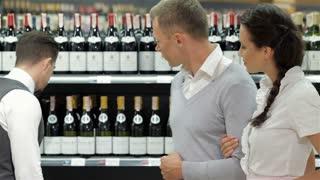 Salesman giving advice on buying bottle of wine