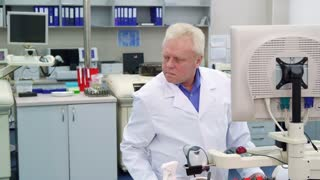 Senior caucasian man controling some process at the laboratory. Aged male scientist working at the science lab. Mature science researcher making calculations