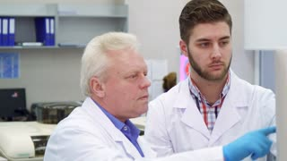 Senior caucasian man pointing his hand on monitor screen at the laboratory. Aged male scientist showing something to his intern on computer. Close up of young lab worker turning face to his mature