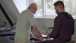 Senior gray man turning on the treadmill at the gym. Young bearded trainer advicing his aged client about running on treadmill. Old caucasian sportsman pressing the buttons on dashboard