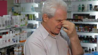 Senior male customer feeling bad at the drugstore. Aged caucasian man massaging his nose between eyes. Old gray man looking for some medicine at the pharmacy