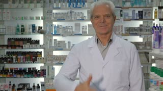 Senior male druggist showing his thumb up at the pharmacy. Gray man gesturing good quality of drugstore. Old man in medical uniform standing against background of working female pharmacist