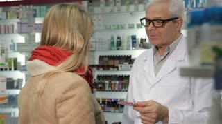 Senior male pharmacist offering pills to female customer at the drugstore. Aged caucasian man in medical uniform giving blister of pills to blond woman. Gray male druggist in glasses telling young