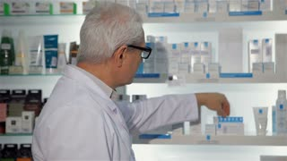 Senior male pharmacist posing at the drugstore. Aged man in medical uniform turning to the camera. Gray male druggist taking off his glasses