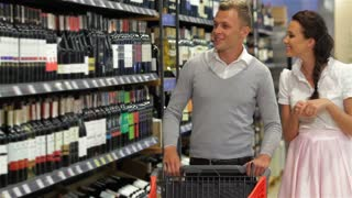 Shoppers choosing bottle of wine