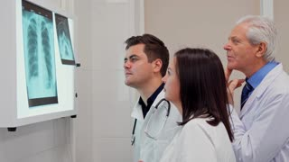 Side view of medical team of three doctors analizing x-ray on x-ray view box. Senior gray male doctor standing behind his two colleagues. Young brunette male medic and mature caucasian female doctor