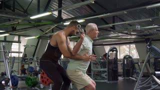 Side view of young male trainer controlling exercises of senior client at the gym. Caucasian bearded guy holding his hands under aged sportsman's arms. Old gray man training under supervision of