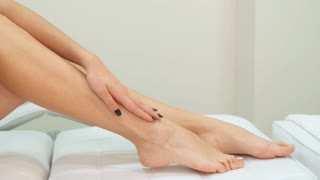 Slim woman stroking her leg on massage table. Young girl demonstrating her slender smooth legs. Close up of fit female client wrapped by white towel at the beauty salon