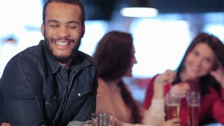 Smiling African man on the background of two girls in a bar