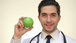 Smiling male doctor with a green apple