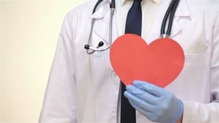 Smiling male doctor with a paper heart