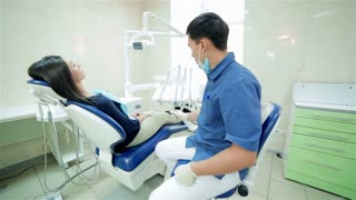 The dentist closer to patient sitting in the dental chair and speaks to her, smiling