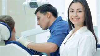 The dentist examines the teeth and smiles at him and the girl-assistant teeth smile directly at the camera and thumb up