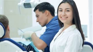 The dentist examines the teeth and the girl-assistant smiles and thumbs up