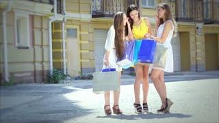 Three beautiful smiling girl shopaholic walking with shopping bags