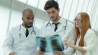 Three confident doctor examining x-ray snapshot of lungs in hospital