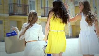 Three cute girls walking hand in hand while shopping