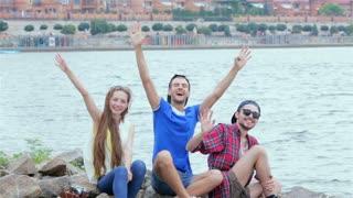 Three friends sitting and waving at the camera