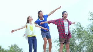 Three friends standing on the rocks at the river and flap their hands