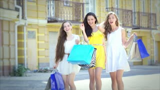 Three girls on a sunny afternoon walk with bags fashion shopping slow motion