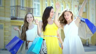 Three happy girls walking along the fashionable boutiques with packages shopping