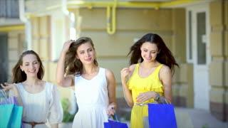 Three hot stuff girls walking with shopping bags