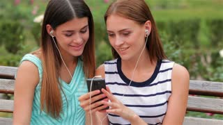 Two attractive girls listening to music
