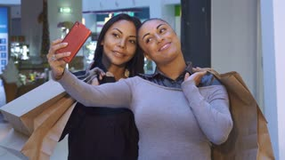 Two beautiful women making selfie with shopping bags. Young african american girls photographing themselves at the mall. Pretty brunette lady holding her smatphone in front of her friend