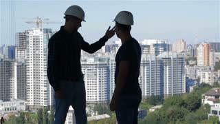 Two builders look at the landscape of high buildings